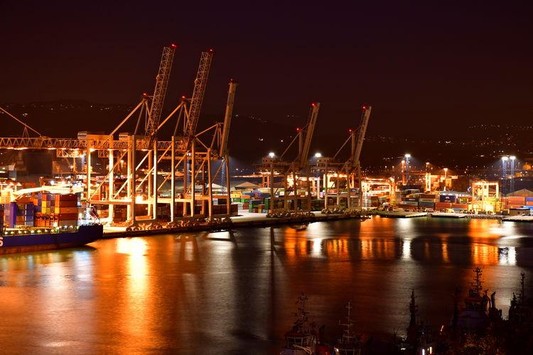 Illuminated harbor by sea against sky at night