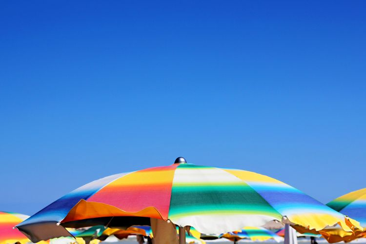 Adult Beach Umbrella Blue Clear Sky Copy Space Day Emotion Flag Group Of People Multi Colored Nature Outdoors People Protection Shade Sky Summer Umbrella The Still Life Photographer - 2018 EyeEm Awards