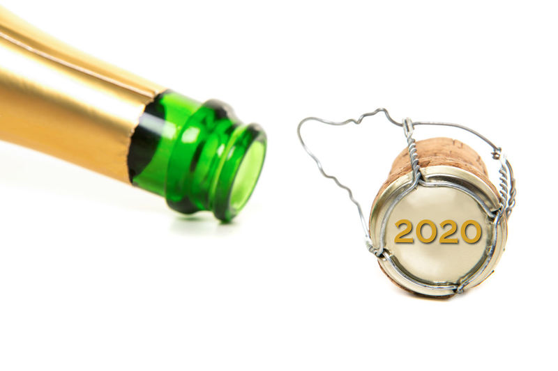 Champagne bottle and cork and with new year 2020 on the cork on a white background New Year's Eve 2020 New Year Champagne White Background Studio Shot Glass - Material Copy Space Cut Out Cork