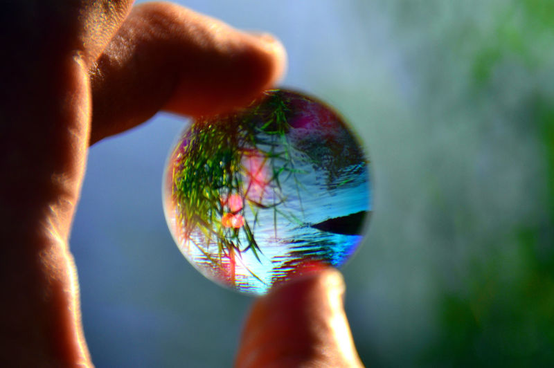 The world within Ball Close-up Day Focus On Foreground Fragility Holding Human Body Part Human Hand Lens Multi Colored One Person Outdoors Real People Round Sphere