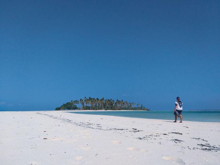 Man walking on beach against clear blue sky