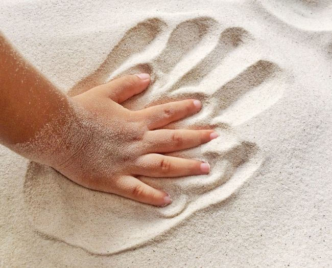 Cropped hand of child on sand at beach