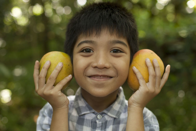 Cute Young Boy Holding Manggo Cheerful Child Childhood Children Only Close-up Cute Day Education Food Front View Fruit Gap Toothed Happiness Headshot Human Body Part Human Hand INDONESIA Looking At Camera Nature One Person Outdoors People Portrait Smiling Yellow
