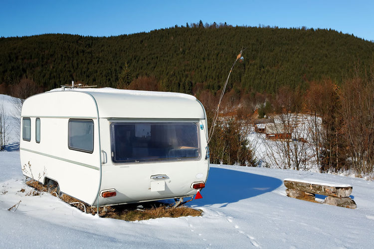 Camper Van On Snow Covered Field By Mountains In Sunny Day