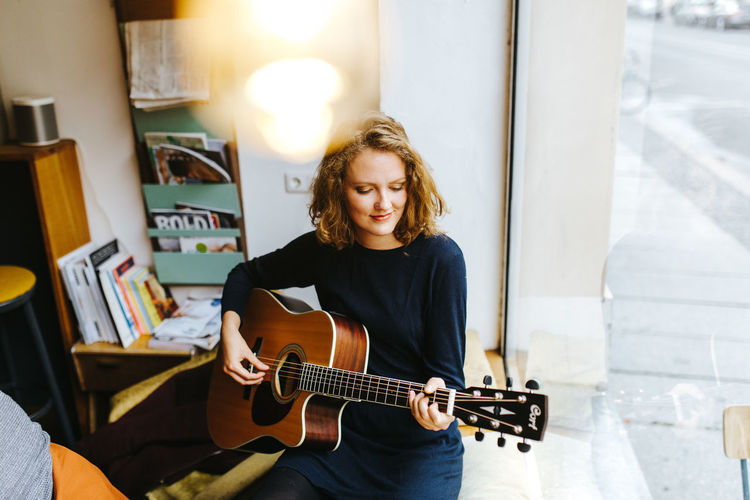 Young woman playing her guitar Light Natural Light Natural Look  Casual Clothing Day Front View Guitar Indoors  Inspiration Inspirational Leisure Activity Lifestyles Music Musical Instrument Musician One Person Playing Plucking An Instrument Real People Smile Woman Portrait Young Adult Young Women