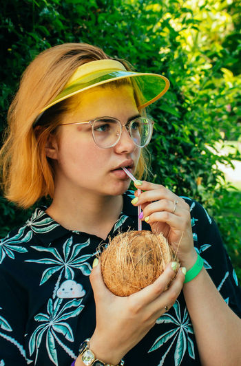 Young woman drinking coconut water with straw