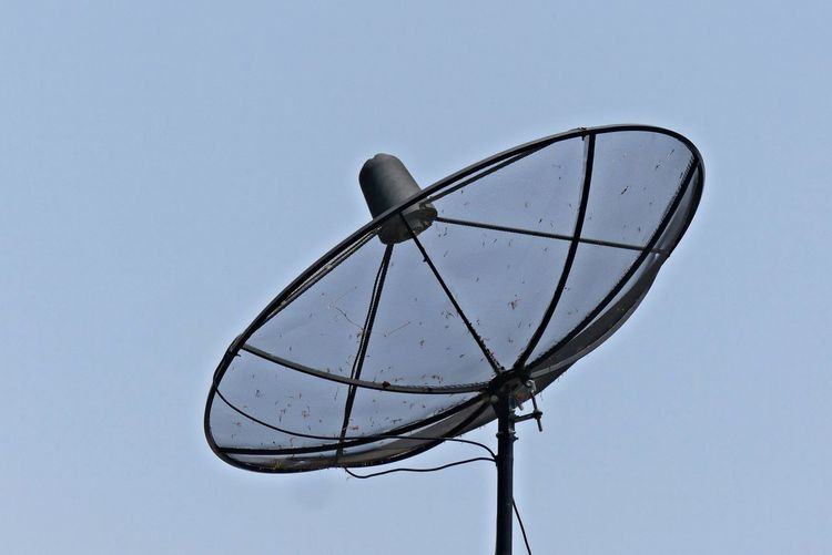 Close up of Satellite Dish on Clear Sky Background Antenna - Aerial Background Close Up Communication Connection Electrical Equipment Global Communications Low Angle View No People Outdoors Satellite Satellite Dish Single Object Sky Technology Telecommunications Equipment Television Aerial