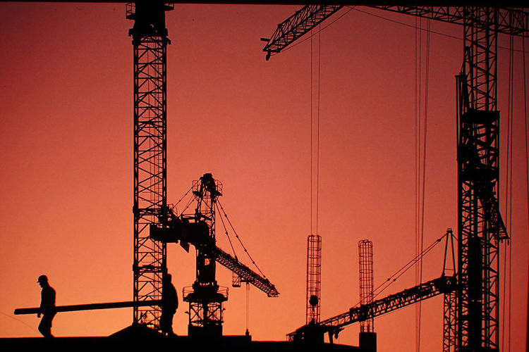 Silhouette of cranes against sky at sunset