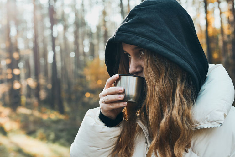 Woman in a hood having break during autumn trip holding cup with hot drink from thermos flask