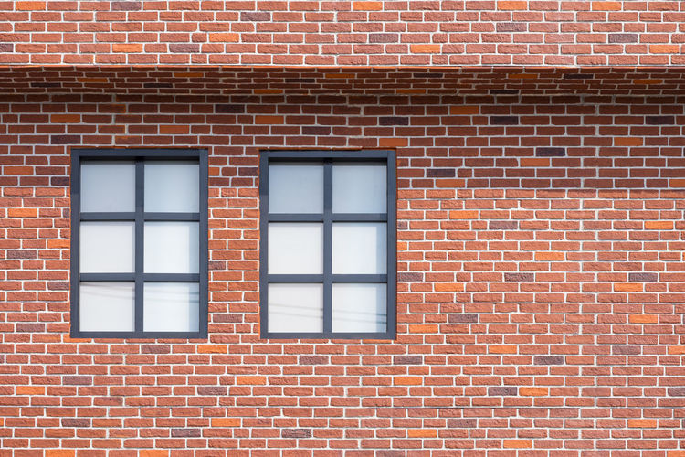 Low angle view of window on brick wall