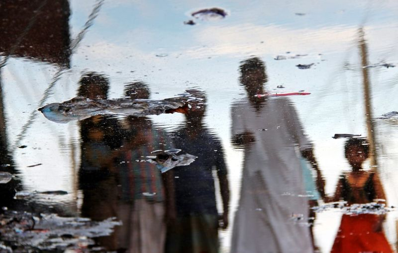 Reflection Of People On Puddle During Monsoon