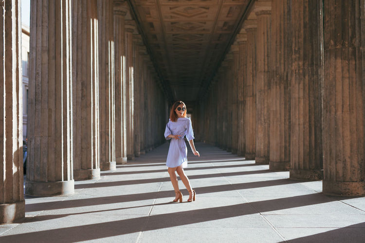 Smiling young woman standing amidst columns
