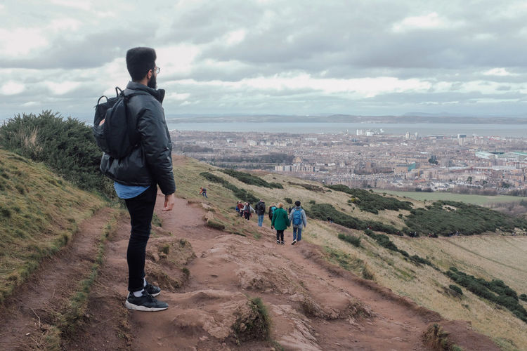 Sky Cloud - Sky Real People Lifestyles Leisure Activity Full Length Nature Men People Day Rear View Casual Clothing Mountain Landscape Standing Land Environment Beauty In Nature Adult Outdoors Arthur's Seat