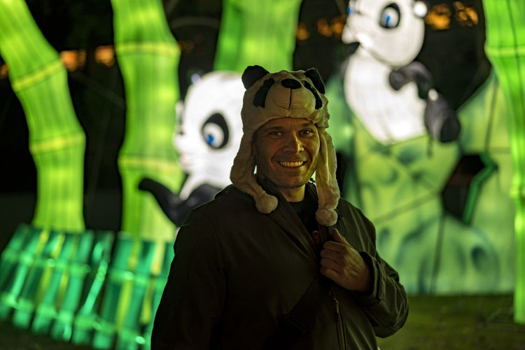 Portrait Of Smiling Man Wearing Panda Cap At Amusement Park
