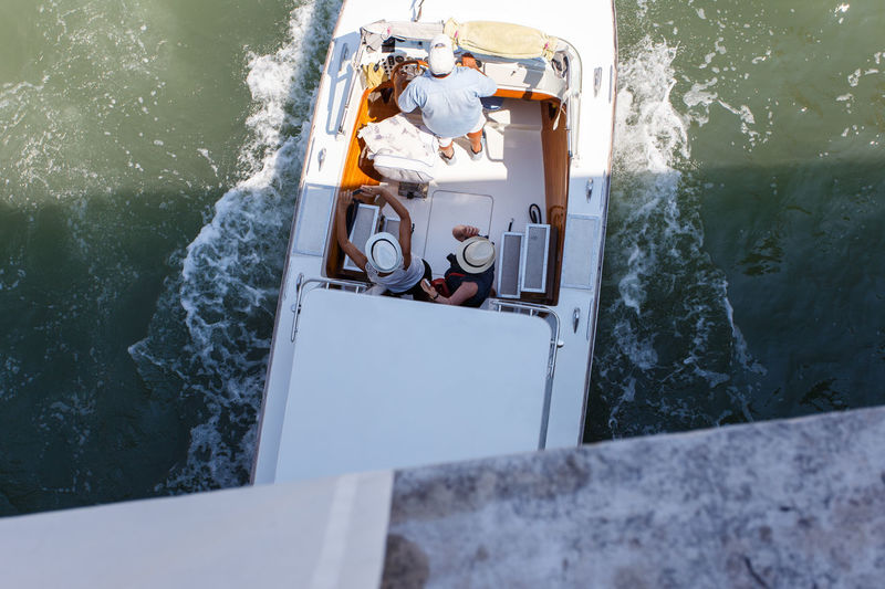 Directly above shot of friends on motorboat sailing on grand canal