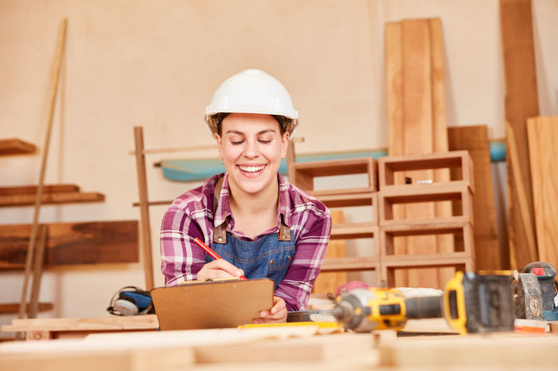 Portrait of smiling man working on wood