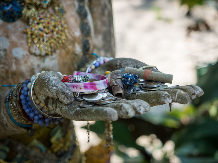 Close-up of donations to buddhist temple in hands of buddha statue, chiang mai, thailand