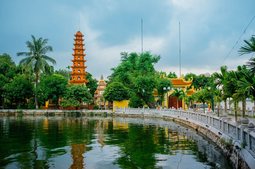 Tran Quoc Pagoda. Pagoda Shrine Architecture Belief Buddhism Building Exterior Built Structure Lake Nature No People Outdoors Palm Tree Place Of Worship Plant Reflection Religion Sky Spirituality Travel Destinations Tree Tropical Climate Water Waterfront