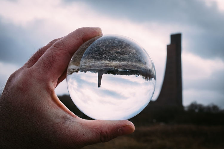 Crystal Ball Reflection Astronomy Beauty In Nature Close-up Crystal Ball Day Focus On Foreground Holding Human Body Part Human Finger Human Hand Magnifying Glass Nature One Person Outdoors People Real People Sky