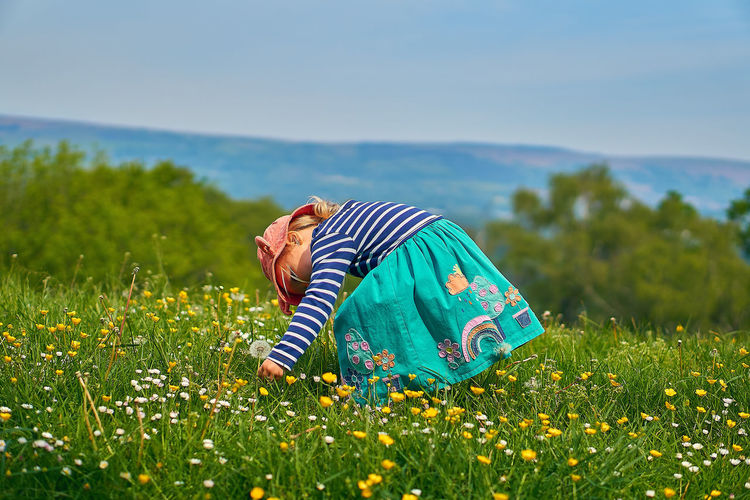 Side view of girl picking flowers while standing on land