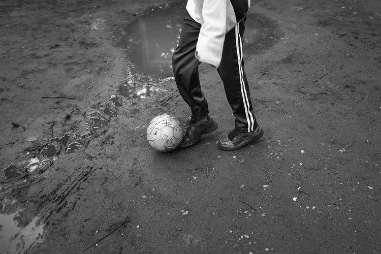 Low section of man playing soccer by puddle on field