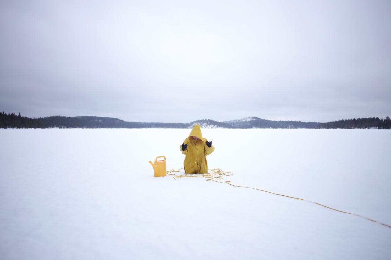 Woman wearing yellow hood stuck in snow
