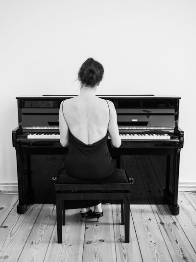 Rear view of young woman playing piano at home