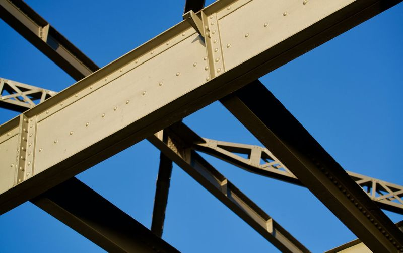 Low angle view of bridge against clear blue sky