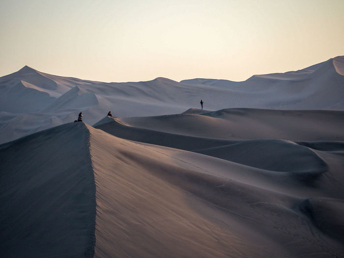 Mid distance view of people standing on sand dunes against clear sky during sunset
