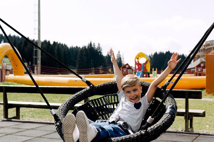 Happy boy sitting on slide at playground