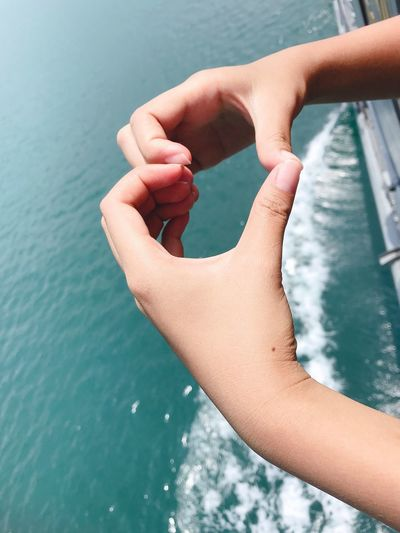 Cropped hands making heart shape over sea