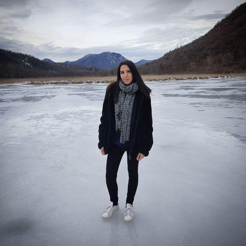 Full length portrait of woman standing on snow against sky
