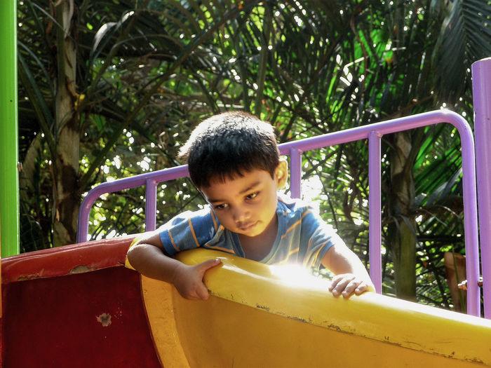 Portrait of boy on slide at playground