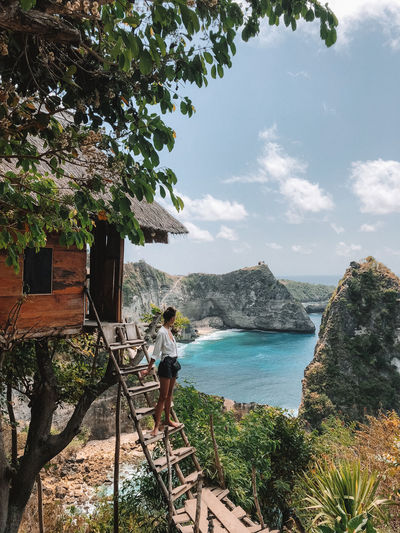 Woman at the tree house in Nusa Penida, Indonesia Water Real People Sky Leisure Activity Lifestyles Beauty In Nature Nature Sea Standing Scenics - Nature Mountain Looking At View Outdoors Woman Girl Nusa Penida Bali Nusa Penida Island Tree House View Adventure Cloud - Sky Ocean Atuh Beach INDONESIA