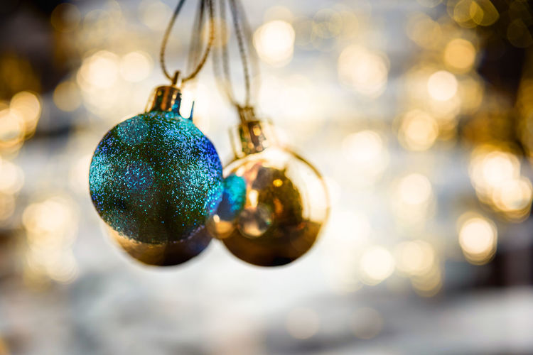 Close-Up Of Baubles Handing Against Christmas Decoration