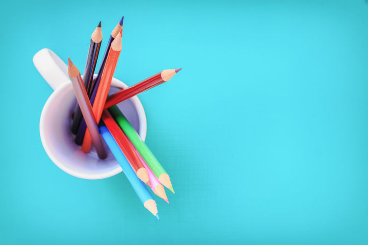 Close-up of multi colored pencils against blue background