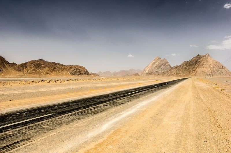 Road leading towards desert against sky