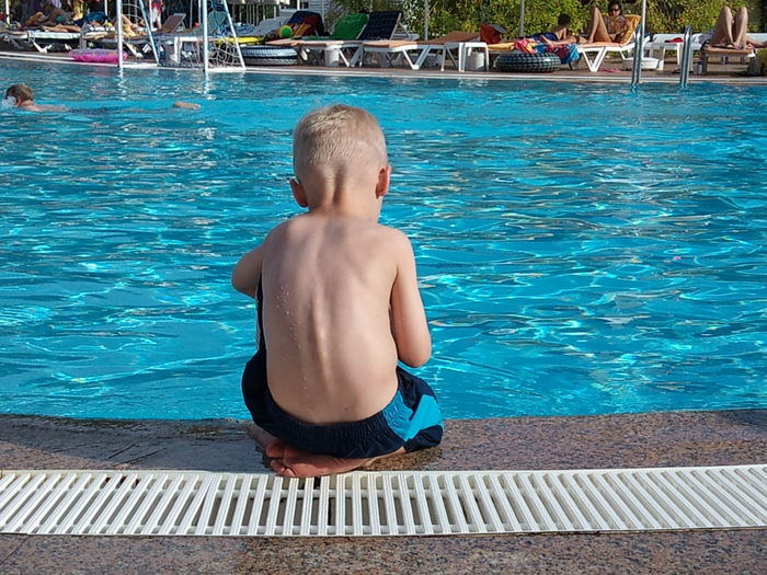 Rear view of boy sitting at poolside