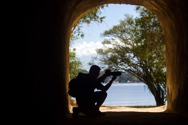 Silhouette man photographing in cave
