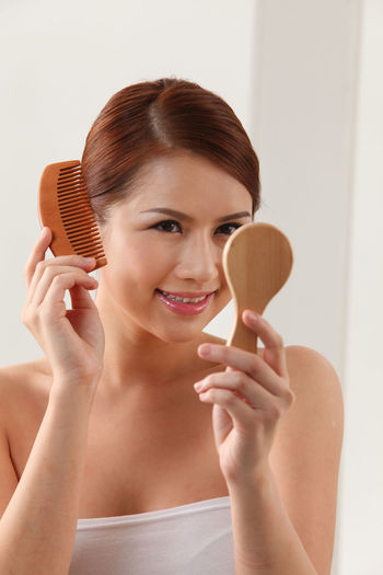 Smiling Young Woman Holding Mirror While Combing Hair Over White Background