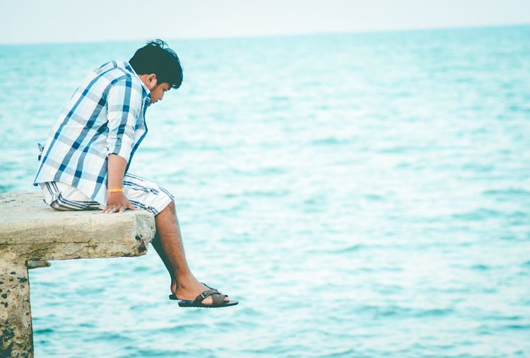 Side view of young man sitting on retaining wall over sea