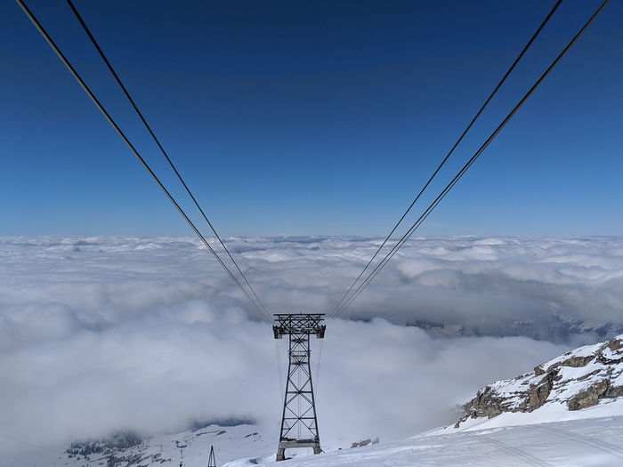 Cable car pylon on snow covered mountain against sky