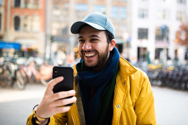 Wireless Technology Smiling Mobile Phone Happiness Smart Phone Technology Portable Information Device Young Adult Portrait Emotion Communication One Person Hat City Connection Adult Toothy Smile Teeth Holding Clothing Outdoors