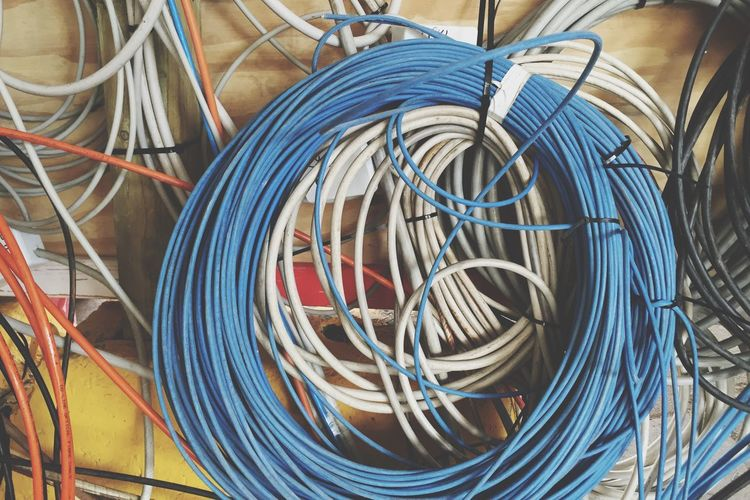 Close-up of tangled cables on wall