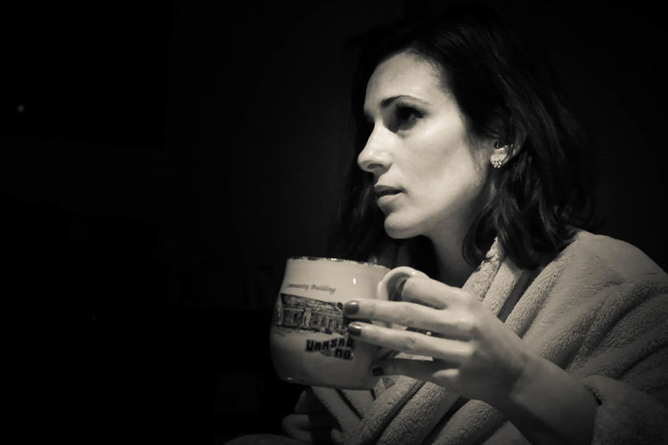Thoughtful woman having coffee cup against black background