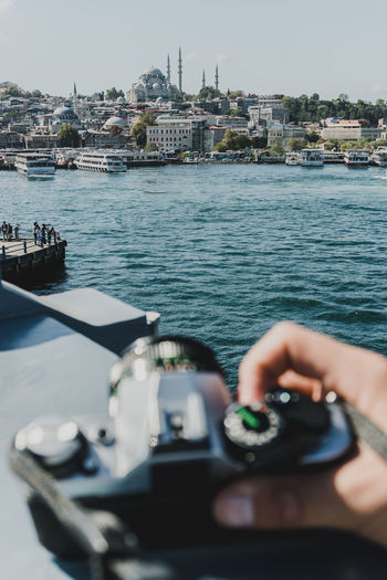 Overlooking the river and a mosque with an analogue camera in hand. - IG: @LostBoyMemoirs (All photos taken on Sony A6300 and edited in Lightroom). Istanbul Turkey Turkish EyeEm Best Shots The Week on EyeEm Streetwise Photography Streetphotography Street Photography People People Watching people and places Travel Human Hand Unrecognizable Person Camera Taking Photos Analogue Photography Analogue Sound