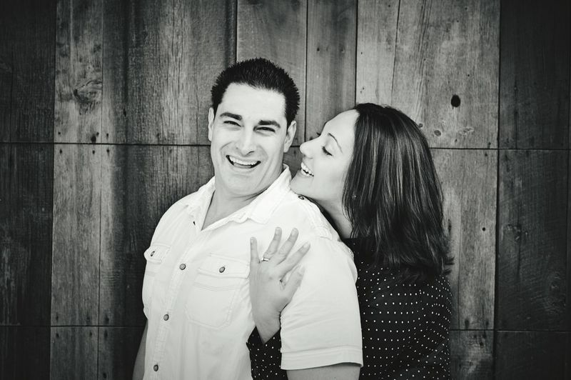 Happy young couple embracing against wooden wall