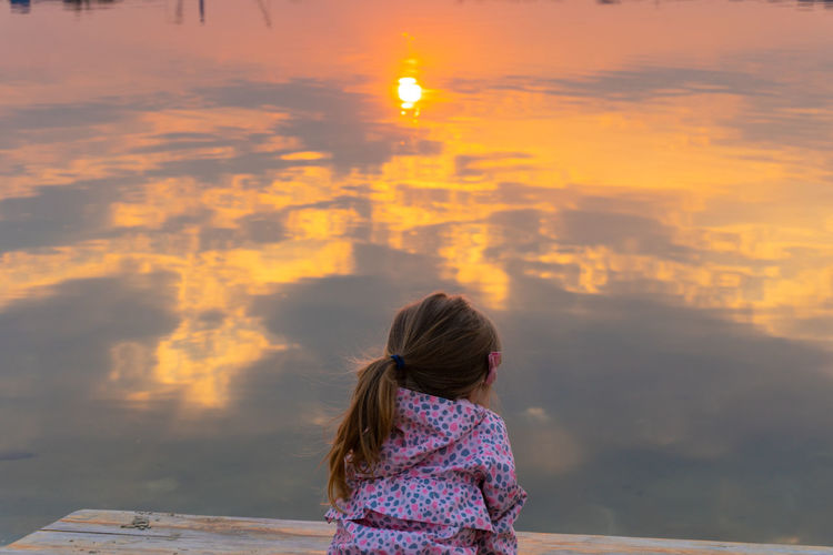 Rear view of girl sitting by lake during sunset