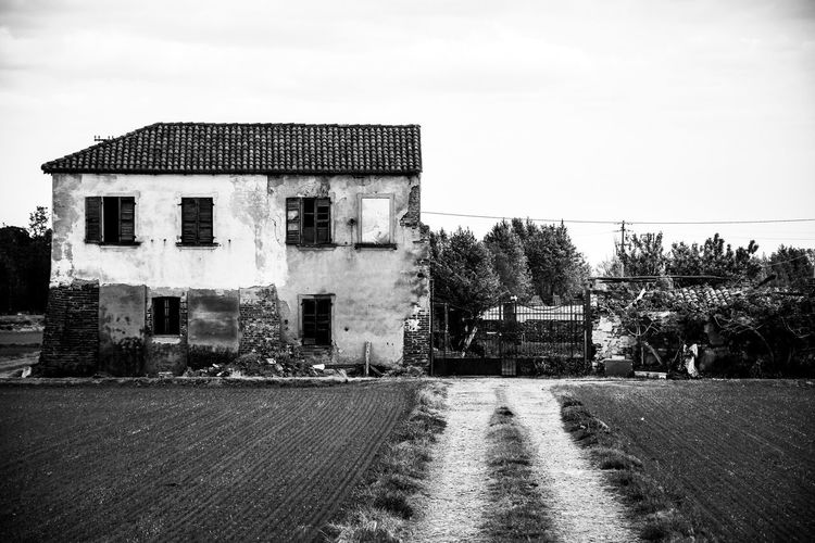 Old building by road against sky