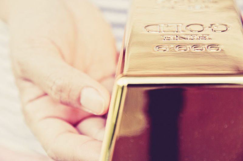 Close-up of hand holding gold bar